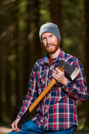 angry forester with a grin with an ax in his hands in the woods Archivio Fotografico