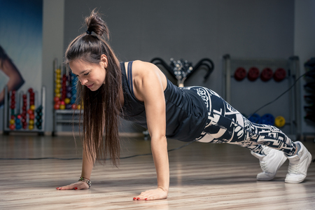 young athletic woman performing an exercise strap on the floor in the gym Stock Photo