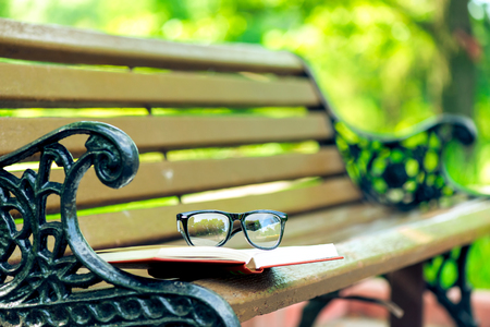 book and glasses lie on the edge of a bench in a summer park Banque d'images - 98720683