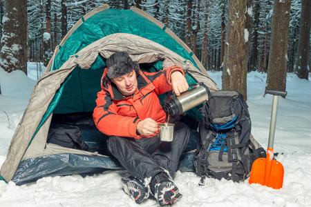 halt in a hike in the winter forest - a break for hot tea Фото со стока