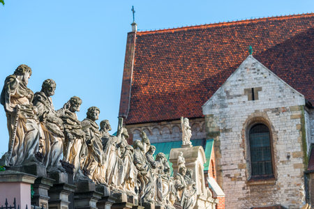 beautiful sculpture of 12 apostles against the background of the Catholic Church in Krakow