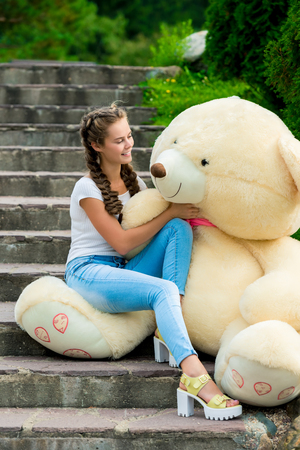 beautiful young girl on the stairs in the park admiring her huge teddy bear