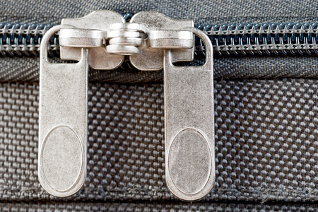 close-up two zipper runners buttoned up on a gray suitcase