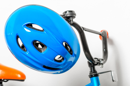 blue helmet for children on the handlebars of a childrens bicycle close-up Stock Photo