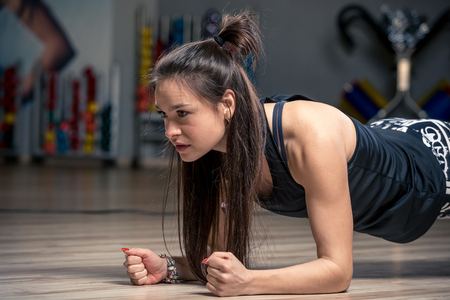 hardy woman performing an exercise strap on the floor in the gym Stock Photo