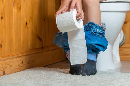 niño con papel higiénico sentado en el inodoro, en el marco del pie