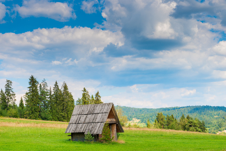 old wooden hut in the field against the backdrop of a beautiful landscape Stockfoto