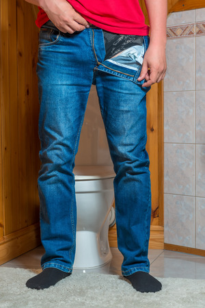 a man takes off his pants in the toilet, a face unrecognizable concept photo Stock Photo