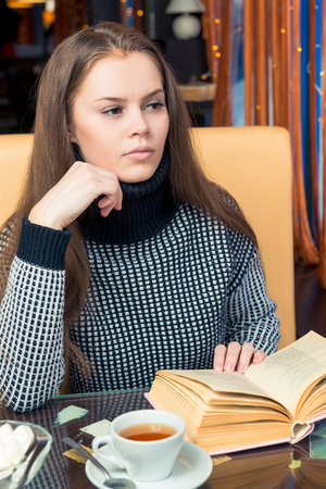 A girl with a book pondered at a table in a cafe, looks out the window Фото со стока