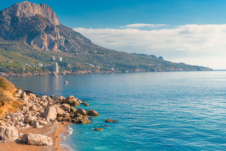 High mountains, rocks and blue calm sea on a sunny day