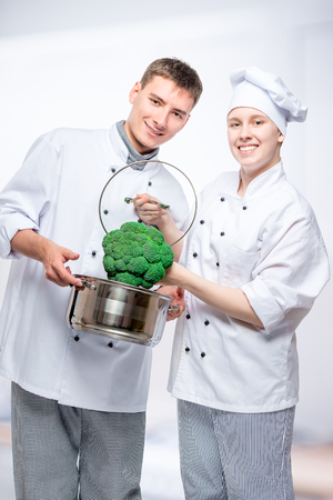 vertical portrait of fellow cooks with saucepan and broccoli in a commercial kitchen