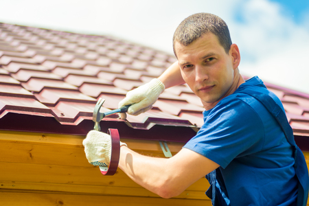 Portrait of a male repairman engaged in repairing a roof of a house, a portrait against a tile Stockfoto