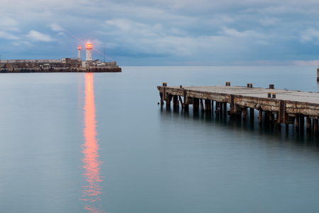 The bright light of the lighthouse on the seashore, right in the frame of the pier at sunset