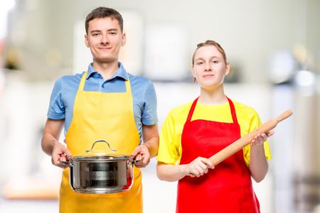 a man with a pan and a woman with a rolling pin portrait in the kitchen
