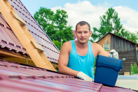 Portrait of a man with a toolbox on the roof of the house during the repair