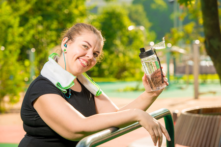 portrait of a happy oversized woman with a bottle of water smiling, portrait after a workout in the park