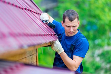 mężczyzna z młotkiem naprawia dach domu, strzelając w plenerze Zdjęcie Seryjne