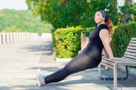 portrait of active happy plump woman performs exercises in the park on a bench