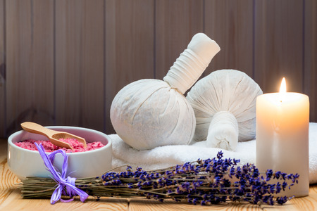 herbal bags with natural lavender and sea salt with a burning candle for a spa, relaxation and romantic atmosphere 写真素材