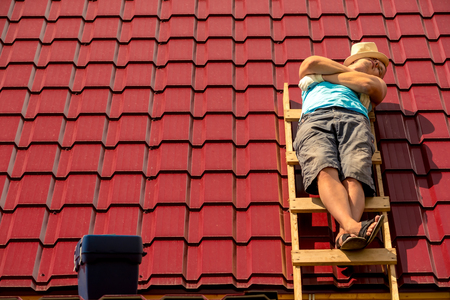 pracownik śpi podczas przerwy opalając się na schodach na dachu domu Zdjęcie Seryjne