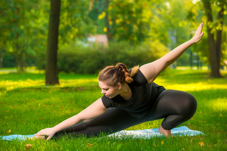 flexible woman plus size in the park on the lawn performs stretching exercises