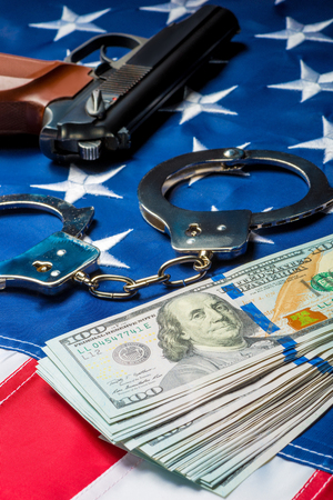 crime and punishment seized money and weapons on the American flag concept photo