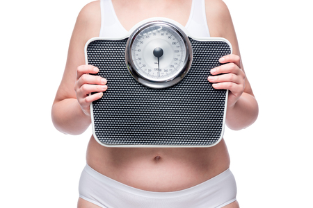 fat woman in underwear with scales in her hands Stock Photo