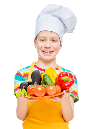 boy cook in a cap with a plate of ingredients - healthy vegetables on white background Imagens