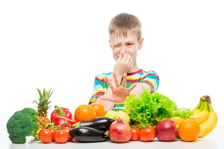 The boy does not like vegetables and fruits, disgust for food concept photo isolated