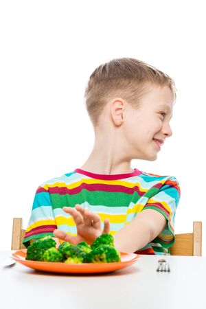 boy moves back plate with tasteless broccoli, portrait on white background isolated