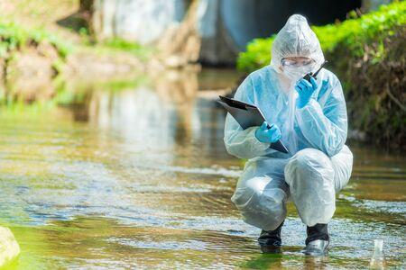Científico ecologista mientras realiza una investigación sobre la contaminación de aguas residuales Foto de archivo
