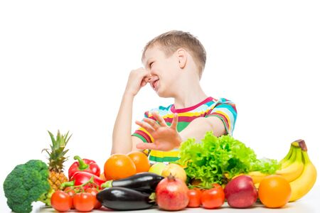 Concept photo of an unloved food - portrait of a boy with an aversion to vegetables and fruits on a white background Banco de Imagens