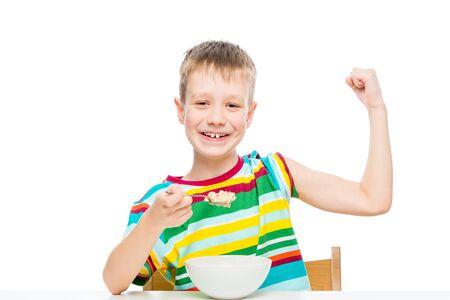 Konzept - richtige Ernährung, ein starker gesunder Junge zeigt Bizeps, isst Brei