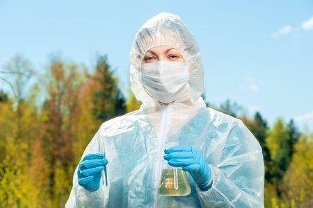 portrait horizontal d'un chimiste-chercheur de la composition de l'eau d'un lac lors d'une épidémie