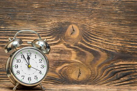 Retro alarm clock on a wooden background shows 12 hours, the space is right Stockfoto - 128398463
