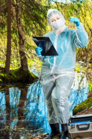 a female ecologist analyzes the state of water in a forest river and records the result of research in a notebook Imagens