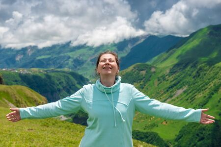 Happy woman enjoys the freedom to travel in the mountains Imagens