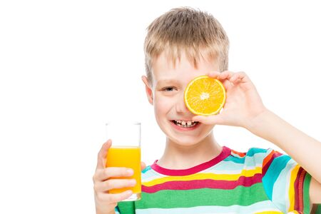 boy with a glass of fresh healthy juice and a slice of orange isolated portrait Imagens