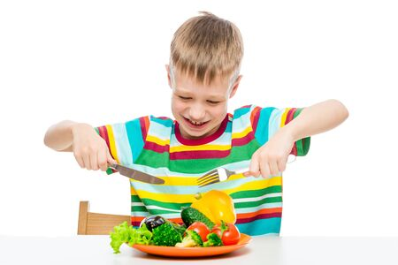 hungry boy 10 years old with a plate of vegetables, concept photo diet and healthy food Imagens