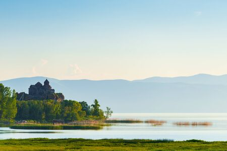 Morning on lake Sevan, view of the monastery on the lake in the rays of the rising sun, landscape of Armenia