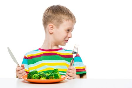 portrait of a boy with a plate of tasteless broccoli on a white background