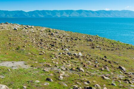 The rocky shore of Lake Sevan, a natural landmark of Armenia on a sunny day Imagens