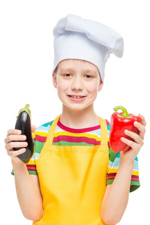 vertical portrait of a child in a cook hat with pepper and eggplant on a white background