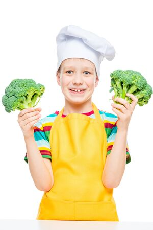emotional portrait of a boy cook in hat and apron with broccoli on white background isolated