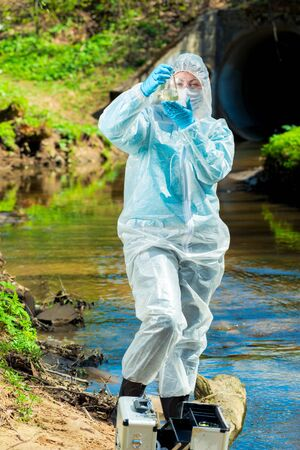 dangerous sewer water, a scientist takes a sample of water in protective clothing Imagens