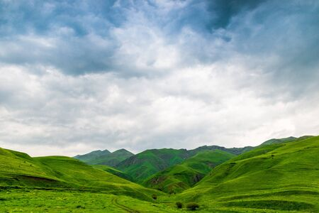 Blue beautiful clouds over the green picturesque mountains of Armenia