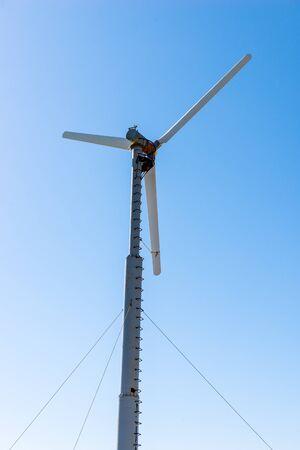 Windmill power generator against blue sky Imagens
