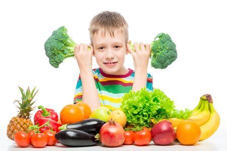 Boy 10 years old with broccoli and a bunch of vegetables and fruits posing in the studio isolated on white background Фото со стока