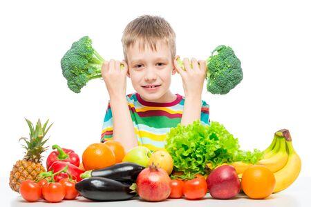 Niño de 10 años con brócoli y un montón de verduras y frutas posando en el estudio aislado sobre fondo blanco. Foto de archivo