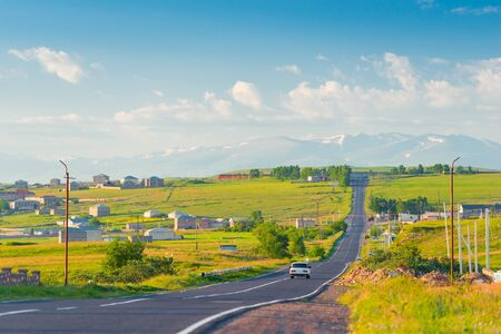 The road, the Armenian village and the view of the snowy peaks of the mountains of Armenia on a summer morning